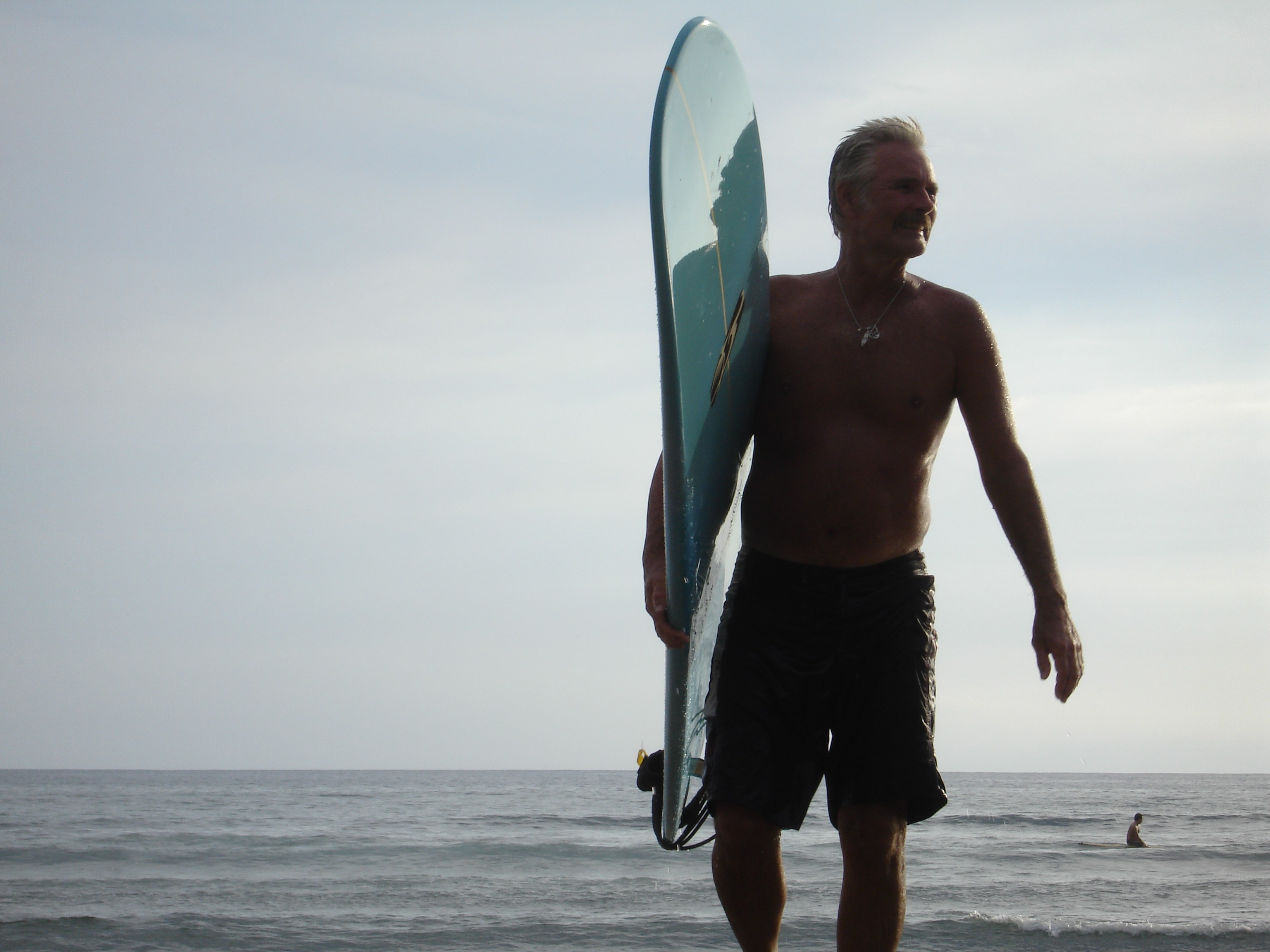 Photo of Mike with his surfboard.